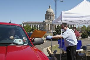 A masked and gloved man takes an envelope from a man in a car in front of a capitol building